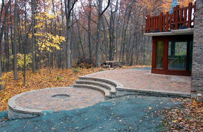 brick paver patio with a fire pit and steps
